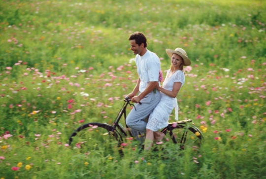 Couple on bicycle in field